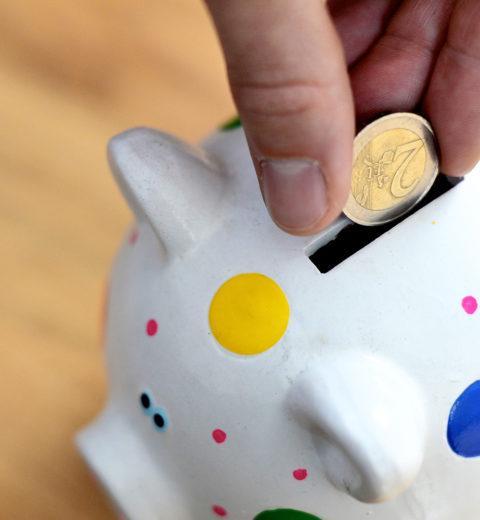 Hand steckt Geld in Sparschwein