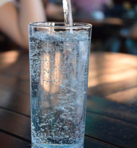 Mineralwasser wird in ein Glas eingegossen.